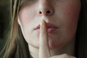 Une image d'une dame avec un doigt sur ses lèvres pour nous demander de nous taire !